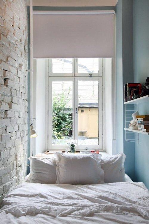 Узкая спальная комната с окном и широкой кроватью
